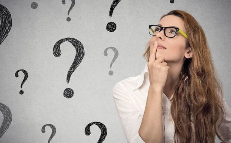 44722071 - thinking business woman with glasses looking up on many questions mark isolated on gray wall background